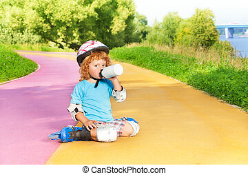 Boy rollerblading and drink water from bottle - Happy thee...