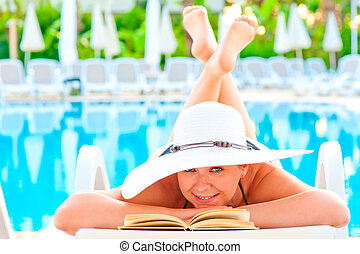 girl in a lounge chair near the pool with his legs crossed...