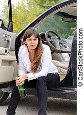 Belligerent drunk woman sitting in the open door of her car...