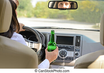 Woman drinking alcohol and driving - View inside a car from...