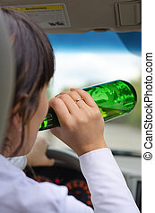 Woman driver drinking while driving on a road - Close up...