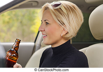 Young female driver drinking alcohol in the car - Young...