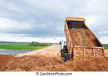 Dump truck unloading soil or sand at construction site...