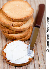 snack crackers with cream cheese and knife on wooden...