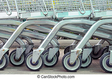row of empty shopping carts in big supermarket - row of...
