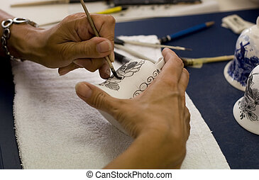 Painting a porcelain - A female artist is working painting a...