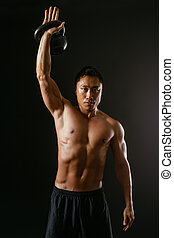 Asian man working out with kettle bell - Photo of an Asian...