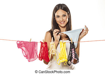 laundry day - Attractive young woman hanging up her...