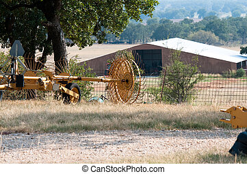Farm equipment with barn in background