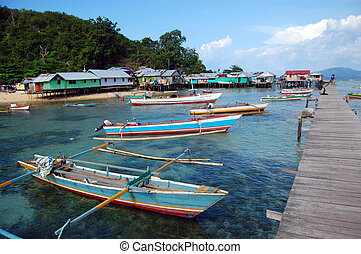 Fishing boats at village timber pier, Papua, Indonesia