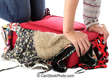 Model Released. Young Woman Packing a Red Suitcase
