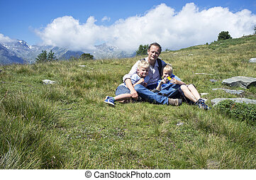 Father and Sons in an alpine meadow - Father sitting with...