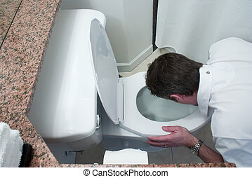 man throwing up in toilet bowl - man kneeling by toilet bowl...