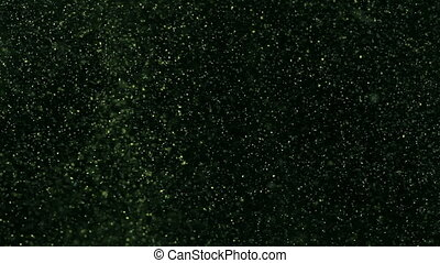 Glitter floating in dyed water - Close-up of glowing green...