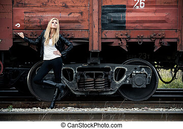 On a railroad - Young woman standing near a train