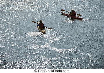 Boys in kayaks. - Aerial of two teenage boys kayaking on...