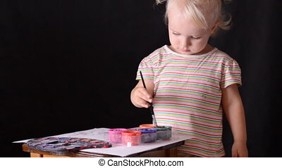 Cute little baby painter on black background.
