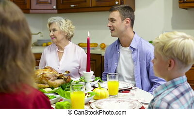 Praying family - Family gathered at festive dinner saying a...