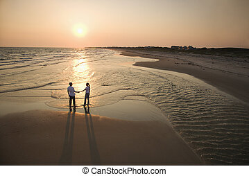 Couple on beach. - Aerial view of romantic couple standing...