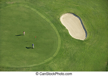 Aerial of golf course. - Aerial view of two people playing...