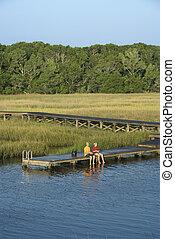 Boys fishing on dock. - Aerial view of two teenage boys...