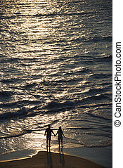 Aerial of couple on beach. - Aerial view of couple holding...