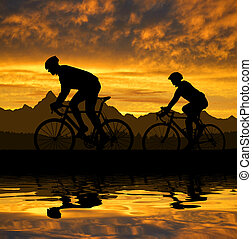 silhouette of the cyclists riding a road bike at sunset