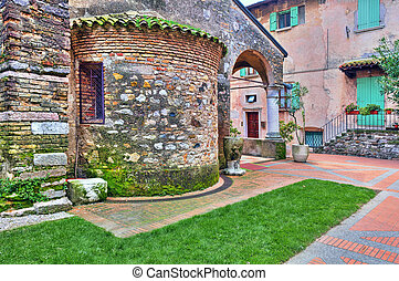 Old medieval church in Sirmione, Italy. - Stone wall of...