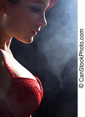 Pretty young woman with red bra looks in profile