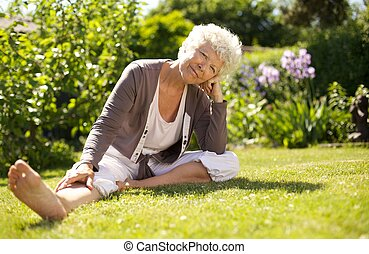Mature woman sitting down on grass comfortably in garden...