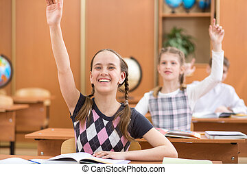 school kids with raised hands at lesson in classroom