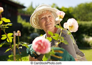 Relaxed mature lady working in her garden - Outdoors