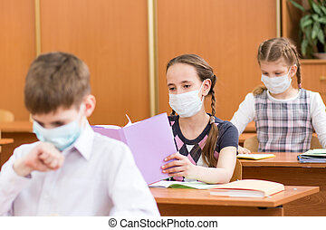 schoolchildren with protection mask against flu virus at...