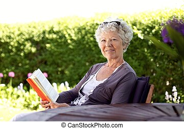 Happy senior woman reading book in the garden