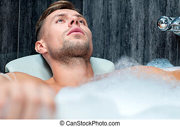 taking bath - Young muscular man taking bath