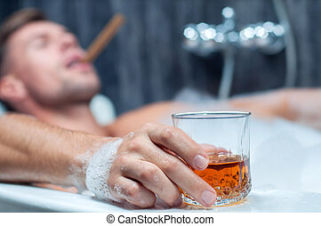 taking bath - young man taking a bath, drinking whiskey and...