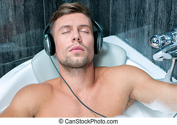 taking bath - young man taking a bath, listening to music...