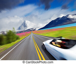Sports car in motion blur - Mountain landscape with road and...