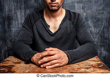 Young man sitting in front of blackboard