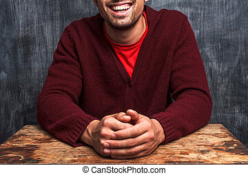 Happy man sitting in front of blackboard