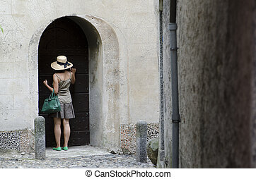 Woman knocking at the door in an old alley