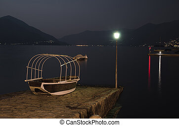 Alpine lake at night - Old fishing boat on a lake with...