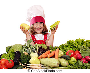 happy little girl cook with peppers and vegetables