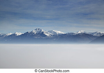 Sea of fog and snow-capped mountain with blue sky and clouds
