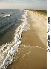 Waves crashing on beach. - Aerial view of waves crashing on...