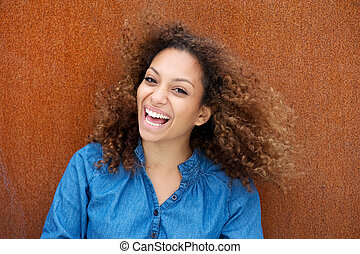 Cheerful young woman smiling with curly hair - Closeup...