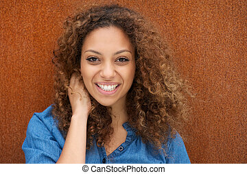 Attractive young woman smiling with hand in hair - Closeup...