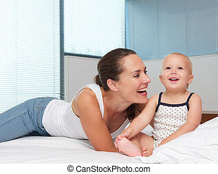 Beautiful mother laughing with cute baby in bed