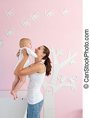 Happy young mother lifting baby from crib at home - Portrait...