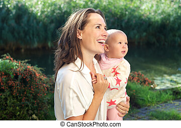 Portrait of a happy mother smiling with cute baby outdoors